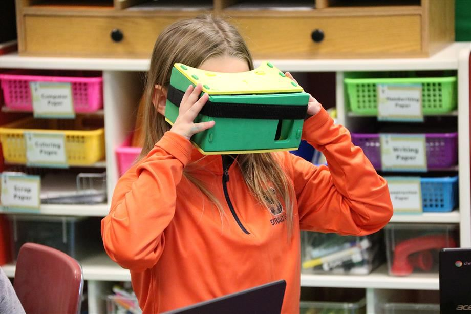 A Phoenix second-grader looks into a virtual reality headset to explore volcanoes .