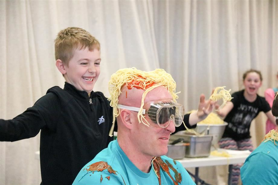 Jason Perkins smiles as he douses physical education teacher Chris Prenoveau with spaghetti