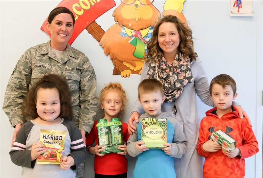 1st-grade teacher Carrie Spoto and some of her students showcase the items they collected for troops