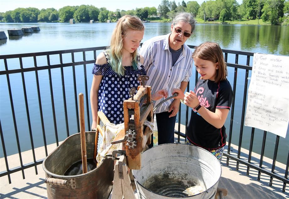 Two fourth-grade girls try doing laundry using an old-fashioned washboard during Canal Days.