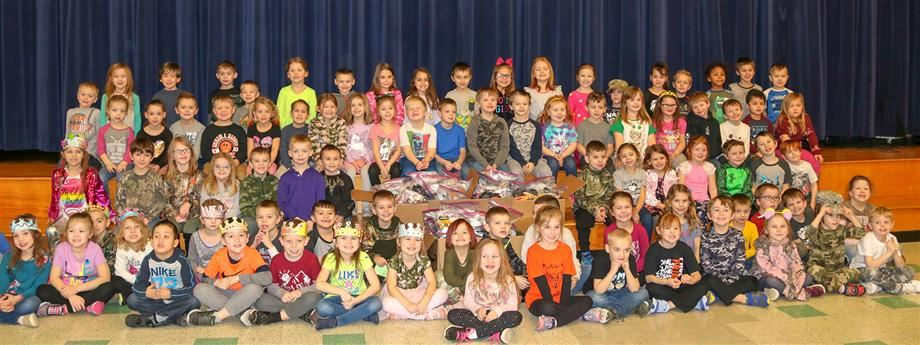 Kindergarten students are all smiles as they show off some of the blessing bags they assembled.