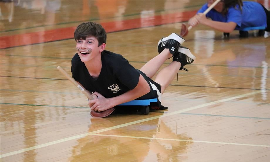Chase McElyea smiles as he propels his scooter across the gym floor using a plunger.