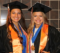 Catherine Musumeci and Natalie Hart in their caps and gowns on graduation day.