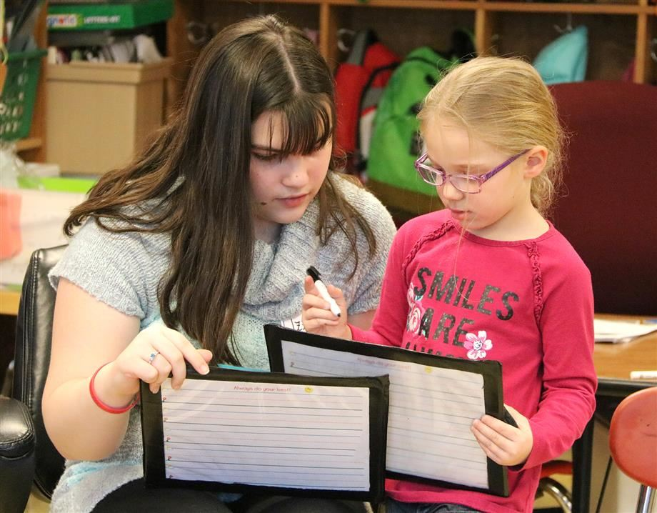 "Izzy Allen works with a student in Mrs. Kompf's class during the annual ""Back to the Future"" event."