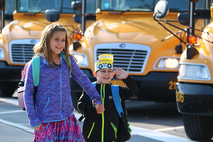 A girl and a boy walk into school on the first day of the 2017-18 school year.