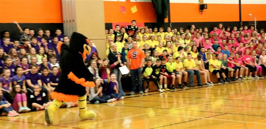 The Phoenix Firebird mascot runs around the gymnasium to pump up a crowd full of students during the Dillon Way celebration.